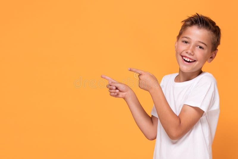 Νέο συναισθηματικό μικρό παιδί στο πορτοκαλί υπόβαθρο στούντιο στοκ φωτογραφίες με δικαίωμα ελεύθερης χρήσης