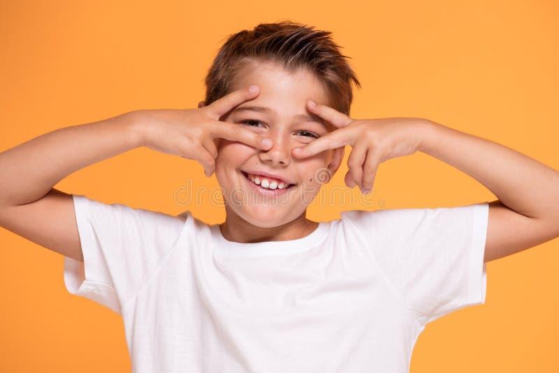 Νέο συναισθηματικό μικρό παιδί στο πορτοκαλί υπόβαθρο στούντιο στοκ εικόνες με δικαίωμα ελεύθερης χρήσης