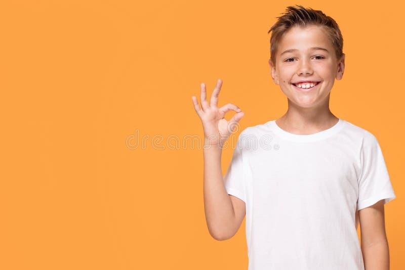 Νέο συναισθηματικό μικρό παιδί στο πορτοκαλί υπόβαθρο στούντιο στοκ εικόνα