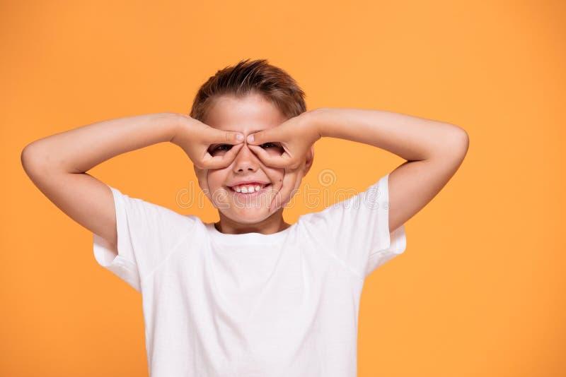 Νέο συναισθηματικό μικρό παιδί στο πορτοκαλί υπόβαθρο στούντιο στοκ φωτογραφία με δικαίωμα ελεύθερης χρήσης