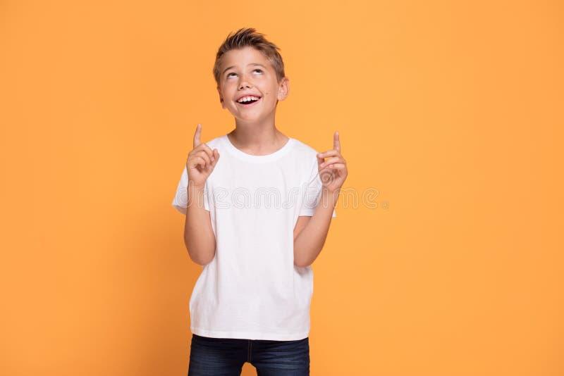 Νέο συναισθηματικό μικρό παιδί στο πορτοκαλί υπόβαθρο στούντιο στοκ εικόνα με δικαίωμα ελεύθερης χρήσης