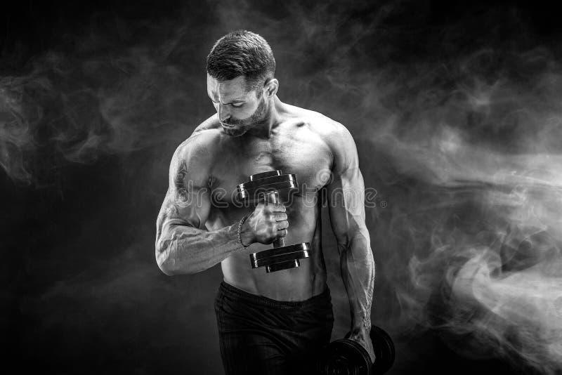 Νέο σχισμένο άτομο bodybuilder με τα τέλεια ABS, ώμοι, δικέφαλοι μυ'ες, στοκ φωτογραφία