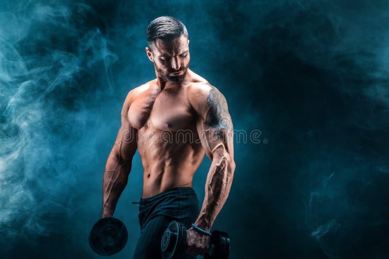 Νέο σχισμένο άτομο bodybuilder με τα τέλειους ABS, τους ώμους, τους δικέφαλους μυς, triceps και τη θωρακική τοποθέτηση με έναν αλ στοκ φωτογραφία με δικαίωμα ελεύθερης χρήσης