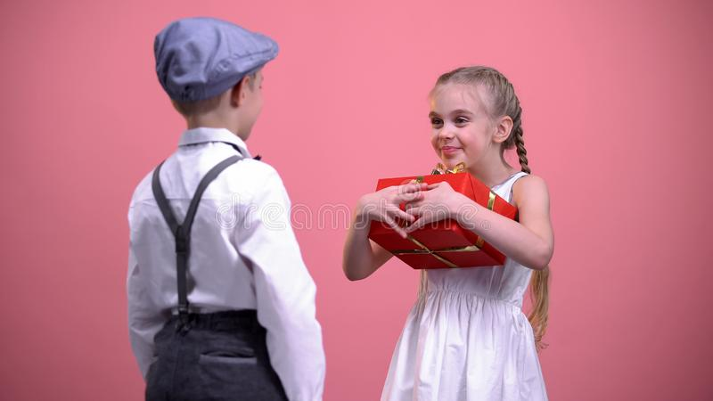 Νέο σχολικό αγόρι που δίνει το τυλιγμένο παρόν στο ευτυχές έκπληκτο κορίτσι, εορτασμός στοκ φωτογραφία με δικαίωμα ελεύθερης χρήσης