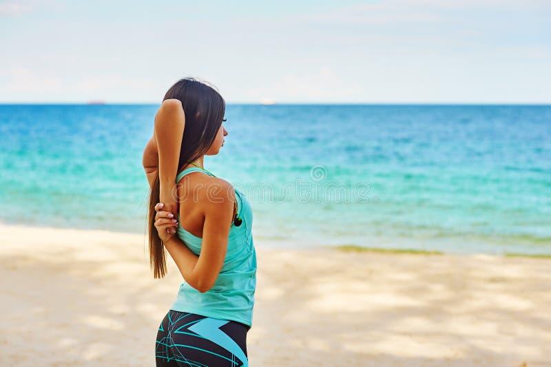 Νέο τέντωμα γυναικών στην παραλία στοκ εικόνα με δικαίωμα ελεύθερης χρήσης