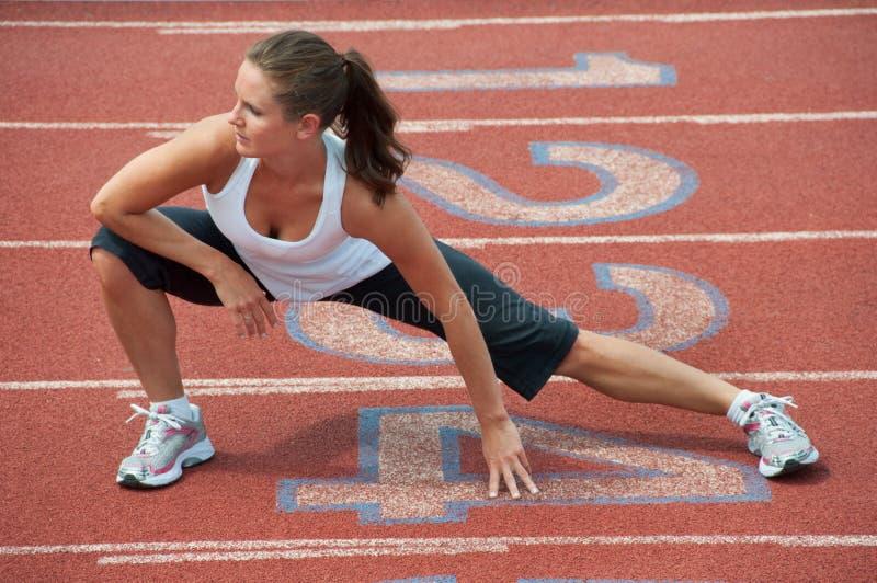 Νέο τέντωμα γυναικών στο τρέξιμο της διαδρομής στοκ φωτογραφίες