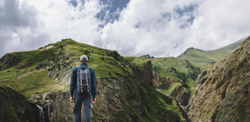 Νέο ταξιδιωτικό άτομο που στέκεται πάνω από τον απότομο βράχο στα βουνά και που απολαμβάνει τη θέα της φύσης, οπισθοσκόπο στοκ φωτογραφίες