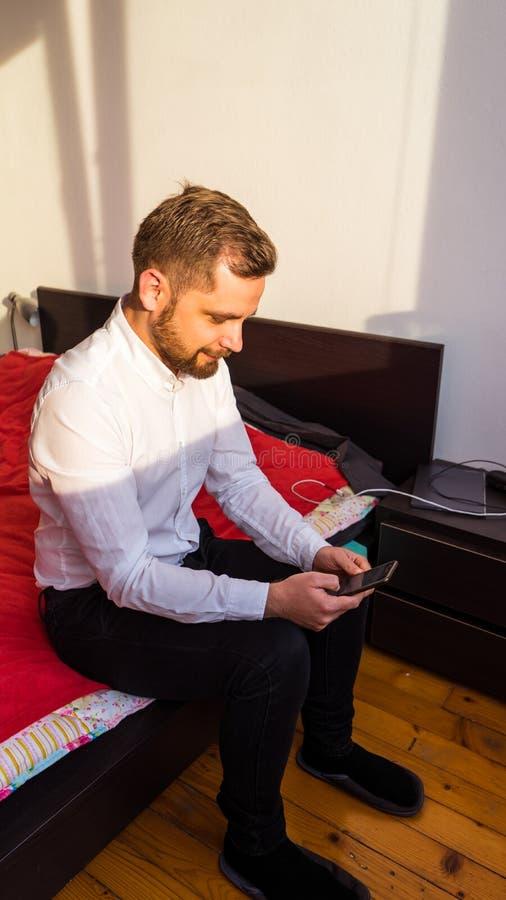νέο τουρκικό άτομο που ελέγχει το smartphone στην κρεβατοκάμαρά του στα ενδύματα σερβιτόρων στοκ φωτογραφίες με δικαίωμα ελεύθερης χρήσης
