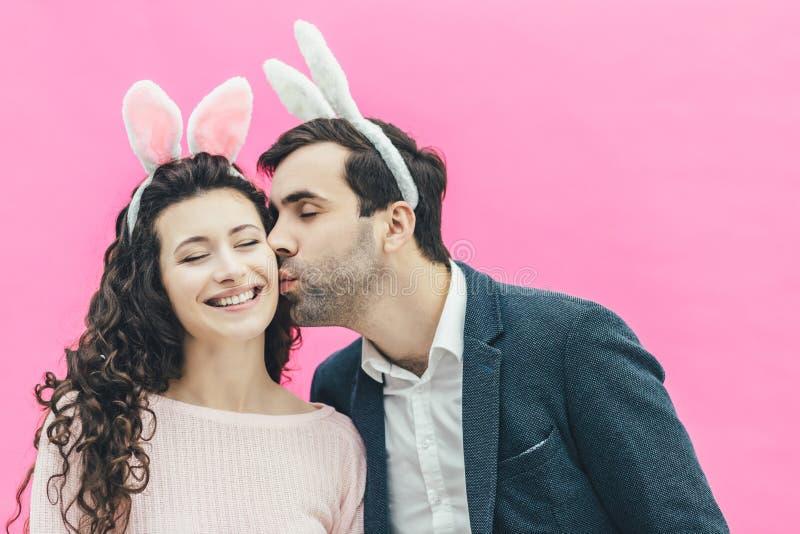 Νέο τρυφερό ζευγάρι που στέκεται σε ένα ρόδινο υπόβαθρο Κατά τη διάρκεια αυτού, στο κεφάλι, των αυτιών λαγουδάκι Ένα άτομο φιλά ή στοκ φωτογραφία με δικαίωμα ελεύθερης χρήσης