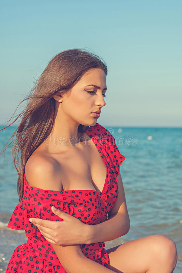 Νέο λυπημένο κορίτσι κοντά στη θάλασσα σε ένα ηλιοβασίλεμα στοκ εικόνα