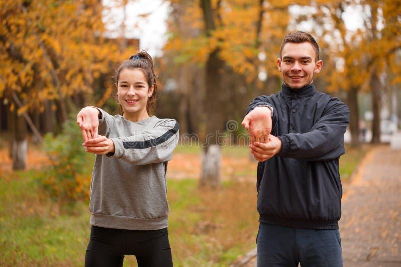 Νέο φίλαθλο ζεύγος που κάνει τον αθλητισμό στο πάρκο φθινοπώρου που κάνει μια άσκηση σε ετοιμότητα προθέρμανσης στοκ φωτογραφία με δικαίωμα ελεύθερης χρήσης