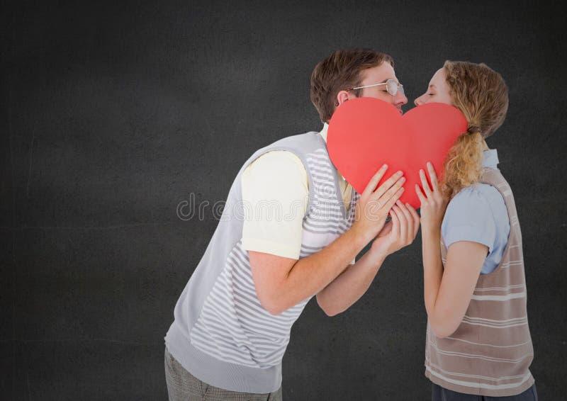 Νέο φίλημα ζευγών πίσω από την κόκκινη καρδιά στοκ εικόνες