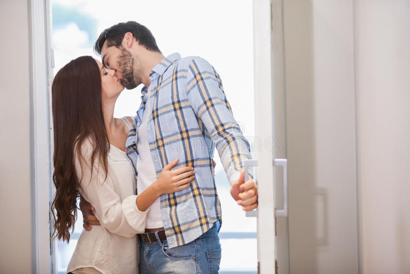 Νέο φιλί ζευγών καθώς ανοίγουν τη μπροστινή πόρτα στοκ εικόνες