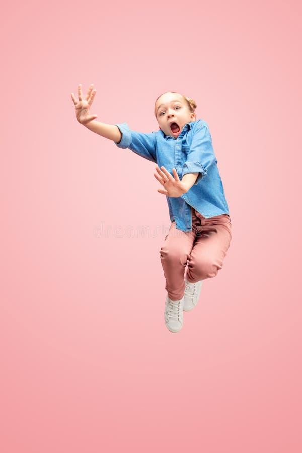 Νέο φοβησμένο καυκάσιο κορίτσι εφήβων που πηδά στον αέρα, που απομονώνεται στο ρόδινο υπόβαθρο στούντιο στοκ εικόνα
