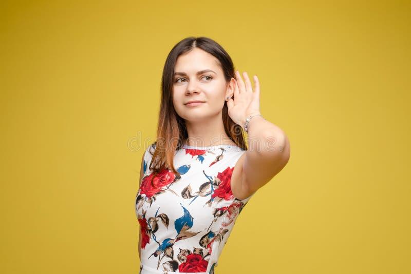 Νέο χέρι γυναικείας εκμετάλλευσης κοντά στο αυτί και το άκουσμα προσεκτικά στοκ εικόνες