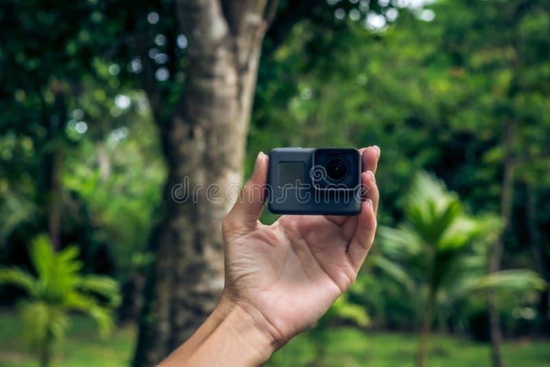 Νέο χέρι γυναικών που κρατά την ακραία κάμερα δράσης στο ασιατικό πράσινο πάρκο Τροπικό νησί του Μπαλί, Ινδονησία στοκ φωτογραφία με δικαίωμα ελεύθερης χρήσης