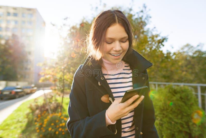 Νέο χαμογελώντας κορίτσι εφήβων με το κινητό τηλέφωνο, ηλιόλουστη ημέρα φθινοπώρου, κορίτσι στο παλτό, χρυσή ώρα στοκ φωτογραφία με δικαίωμα ελεύθερης χρήσης