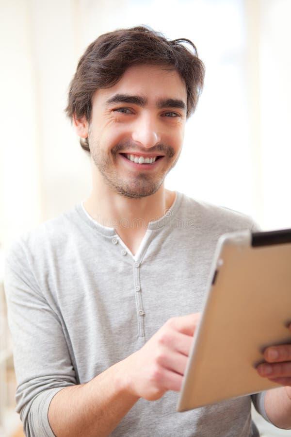 Νέο χαμογελώντας άτομο που χρησιμοποιεί μια ταμπλέτα στοκ εικόνες
