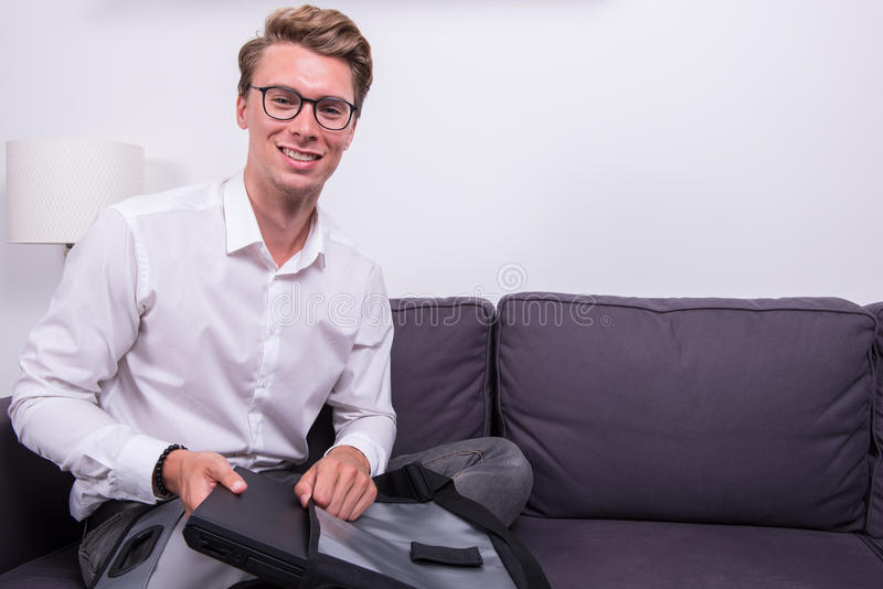 Νέο χαμογελώντας επιχειρησιακό άτομο που συσκευάζει την τσάντα του στον καναπέ στοκ εικόνα