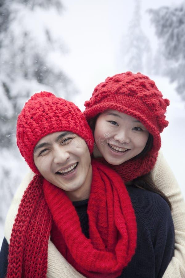 Νέο χαμογελώντας ζεύγος στο χιόνι στο κόκκινο στοκ φωτογραφία με δικαίωμα ελεύθερης χρήσης