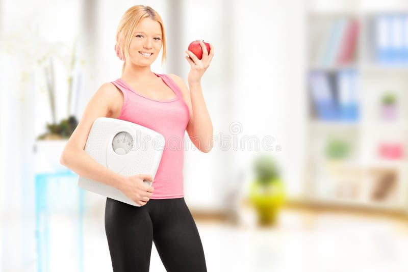 Νέο χαμογελώντας θηλυκό που κρατά μια κλίμακα βάρους και ένα μήλο, στο hom στοκ εικόνες