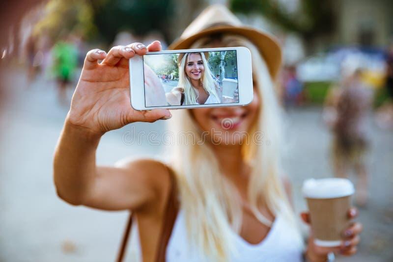 Νέο χαμογελώντας κορίτσι που κάνει selfie στεμένος στην οδό στοκ εικόνες