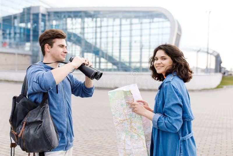 Νέο χαριτωμένο ζεύγος - ένα αγόρι και ένα κορίτσι που περπατούν γύρω από την πόλη με έναν χάρτη και τις διόπτρες στα χέρια του Οι στοκ φωτογραφία με δικαίωμα ελεύθερης χρήσης