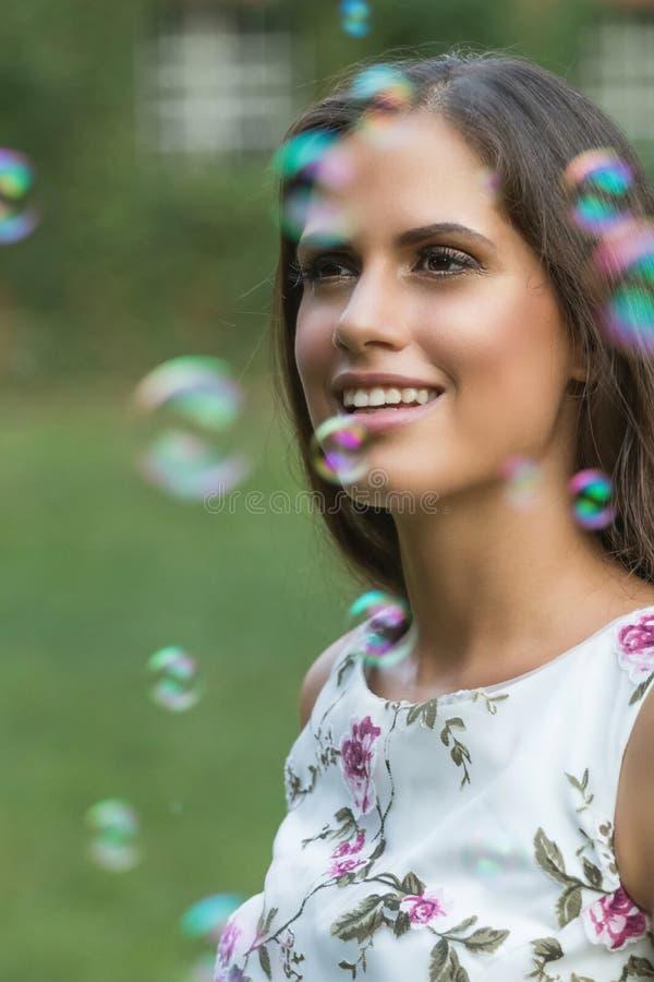 Νέο χαριτωμένο κορίτσι brunette που χαμογελά στο πάρκο μπλε τονικότητα δομών σαπουνιών φυσαλίδων στοκ εικόνες