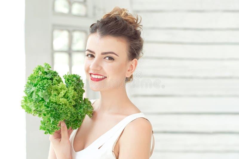 Νέο χαριτωμένο χαμογελώντας κορίτσι που κρατά το οργανικό πράσινο μαρούλι φύλλων κοντά στο πρόσωπο Έννοια Healtlife στοκ εικόνα