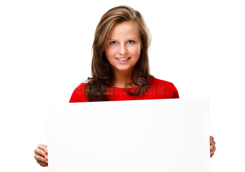 Νέα ελκυστική γυναίκα πίσω από το κενό χαρτόνι στην άσπρη ανασκόπηση στοκ εικόνα με δικαίωμα ελεύθερης χρήσης