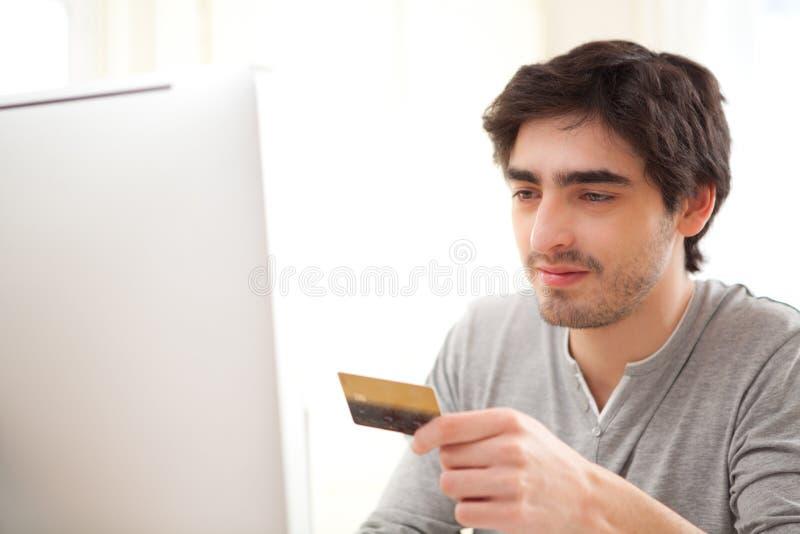 Νέο χαλαρωμένο άτομο που πληρώνει on-line με την πιστωτική κάρτα του στοκ φωτογραφία