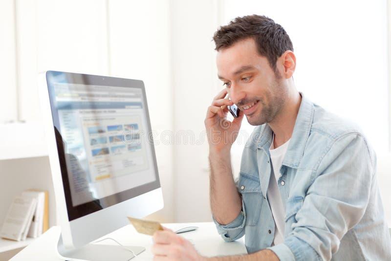 Νέο χαλαρωμένο άτομο που πληρώνει on-line με την πιστωτική κάρτα του στοκ εικόνα