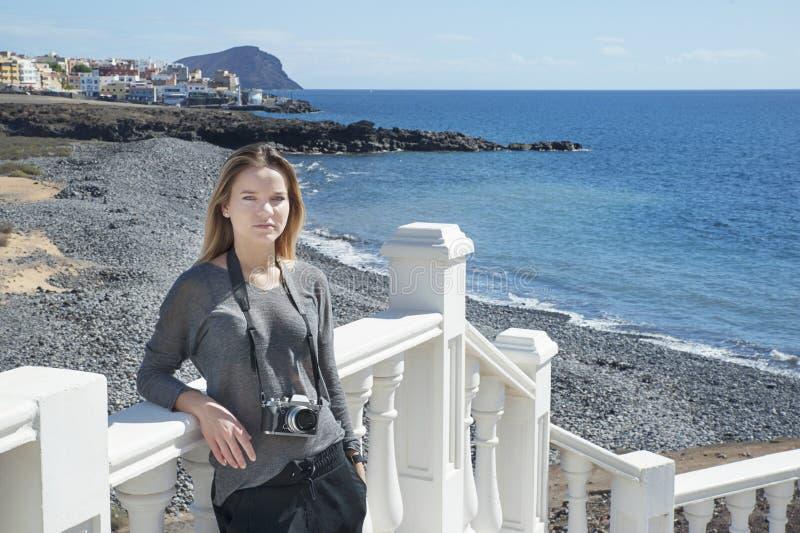 Νέο χιλιετές θηλυκό του καυκάσιου έθνους που κρατά μια ψηφιακή, επαγγελματική κάμερα γύρω από το λαιμό της στοκ εικόνα με δικαίωμα ελεύθερης χρήσης