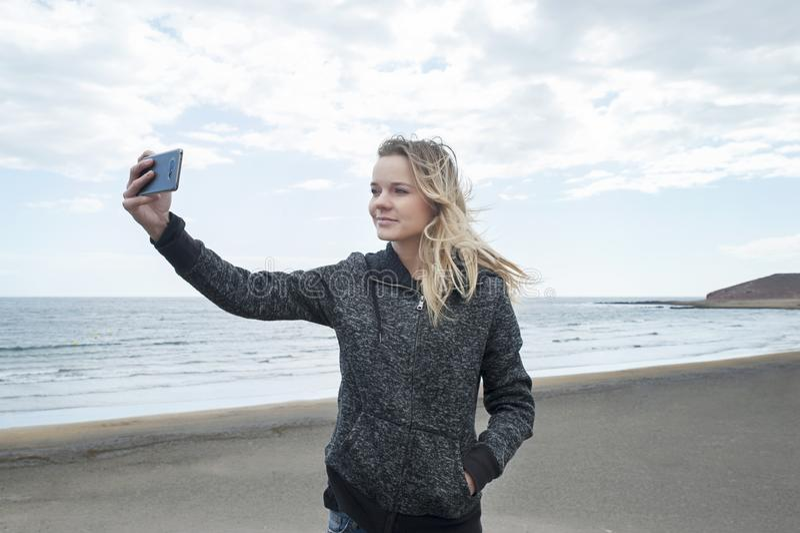 Νέο χιλιετές θηλυκό του καυκάσιου έθνους που παίρνει ένα selfie στην παραλία EL Medano, Tenerife, Κανάρια νησιά, Ισπανία στοκ φωτογραφίες με δικαίωμα ελεύθερης χρήσης