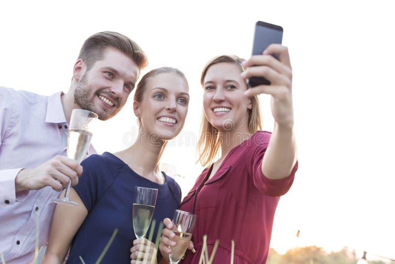 Νέο χύνοντας κρασί επιχειρηματιών για τη επιχειρηματία κατά τη διάρκεια του κόμματος επιτυχίας στο πεζούλι στοκ εικόνες