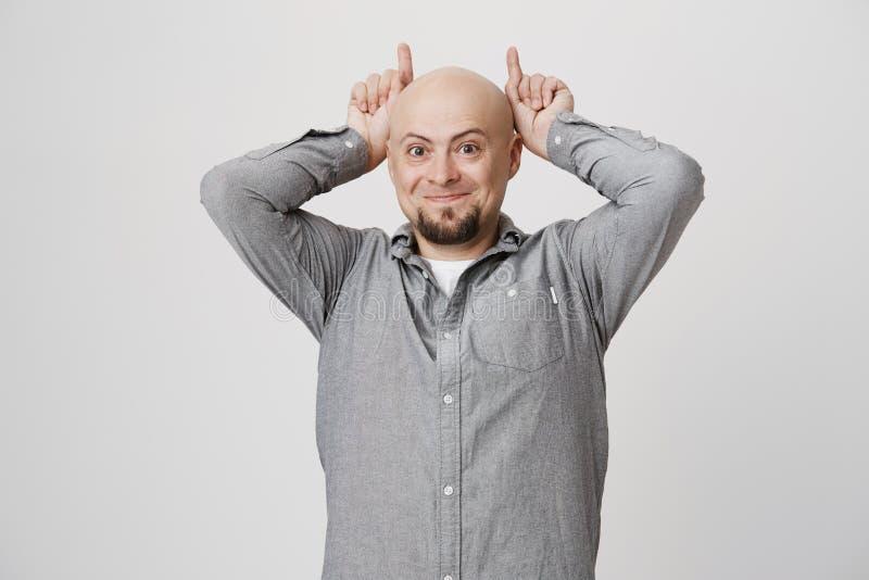 Νέο όμορφο άτομο με μια γενειάδα που κρατά τα χέρια του επάνω από το κεφάλι που κάνει τα κέρατα διαβόλων και που χαμογελά πέρα απ στοκ εικόνα