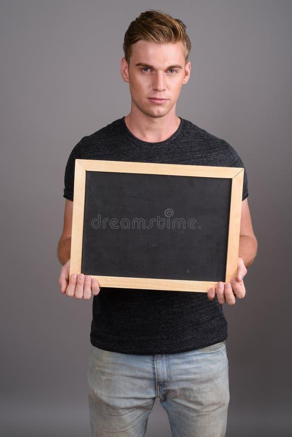 Νέο όμορφο άτομο με τα ξανθά μαλλιά που φορούν το γκρίζο πουκάμισο ενάντια σε GR στοκ φωτογραφίες