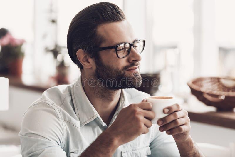 Νέο όμορφο άτομο με το φλιτζάνι του καφέ στον καφέ στοκ φωτογραφίες