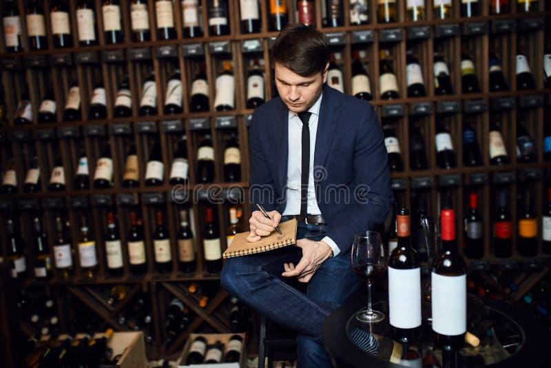 Νέο όμορφο άτομο που διαχειρίζεται τον κατάλογο του κελαριού κρασιού στοκ φωτογραφίες με δικαίωμα ελεύθερης χρήσης