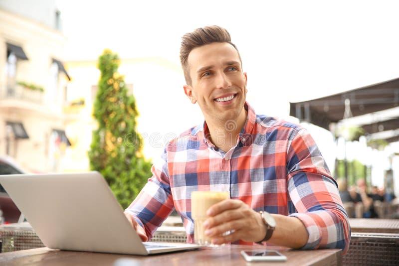 Νέο όμορφο άτομο που εργάζεται με το lap-top στο γραφείο στον καφέ στοκ φωτογραφίες με δικαίωμα ελεύθερης χρήσης