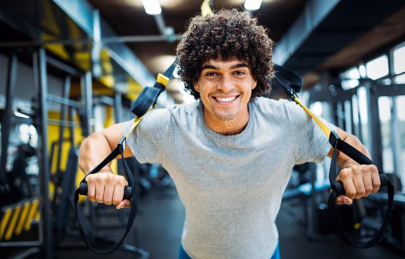 Νέο όμορφο άτομο που κάνει τις ασκήσεις στη γυμναστική στοκ εικόνα