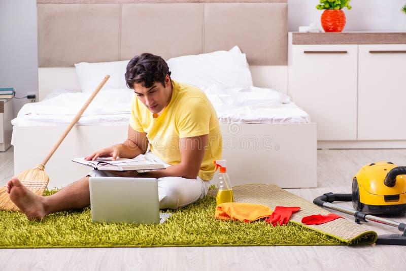 Νέο όμορφο άτομο που καθαρίζει την κρεβατοκάμαρα και που κάθεται στο compu στοκ εικόνα