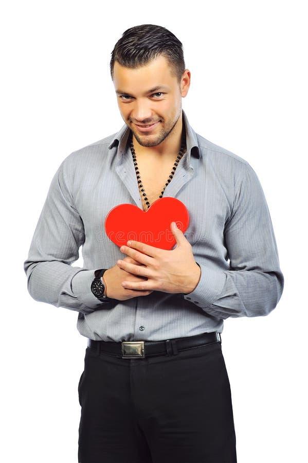 Νέο όμορφο άτομο που κρατά ένα κόκκινο διαμορφωμένο καρδιά παιχνίδι στοκ εικόνες