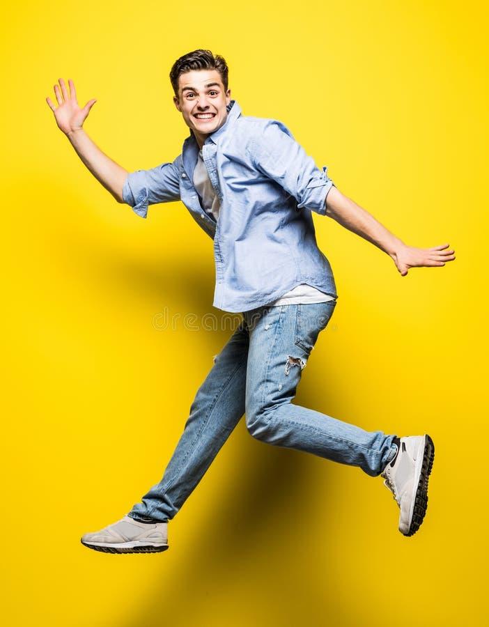 Νέο όμορφο άτομο που πηδά στο κίτρινο υπόβαθρο Άλμα, ελευθερία, καλοκαίρι στοκ φωτογραφίες με δικαίωμα ελεύθερης χρήσης