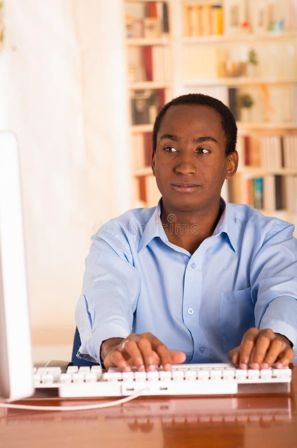 Νέο όμορφο άτομο που φορά την μπλε συνεδρίαση πουκάμισων γραφείων από το γραφείο υπολογιστών που δακτυλογραφεί και που φαίνεται χ στοκ εικόνα με δικαίωμα ελεύθερης χρήσης