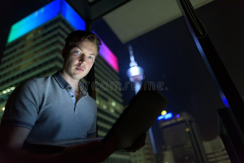 Νέο όμορφο άτομο που χρησιμοποιεί το lap-top ενάντια στο παράθυρο γυαλιού με την άποψη ο στοκ εικόνα