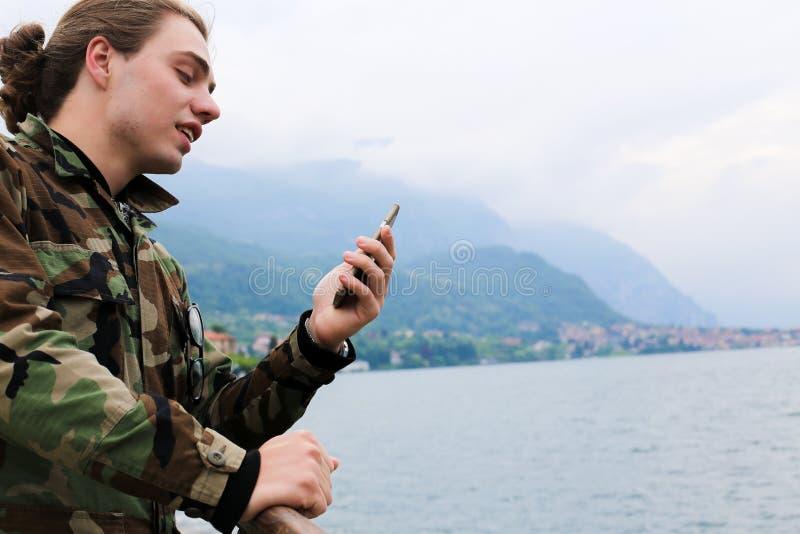 Νέο όμορφο άτομο που χρησιμοποιεί το smartphone κοντά στη λίμνη Como και το βουνό Άλπεων στο υπόβαθρο στοκ φωτογραφία με δικαίωμα ελεύθερης χρήσης
