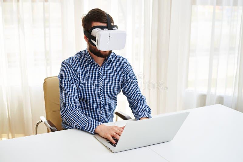 Νέο όμορφο άτομο στα γυαλιά εικονικής πραγματικότητας που λειτουργούν στην περιτύλιξή του στοκ φωτογραφίες