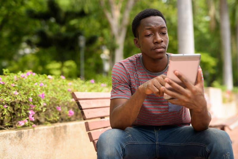 Νέο όμορφο αφρικανικό άτομο που χρησιμοποιεί την ψηφιακή ταμπλέτα στο πάρκο στοκ εικόνες