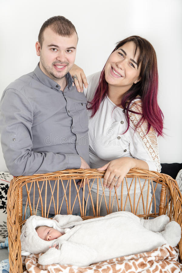 Νέο όμορφο ζεύγος με το νέο μωρό στο σπίτι στοκ εικόνα